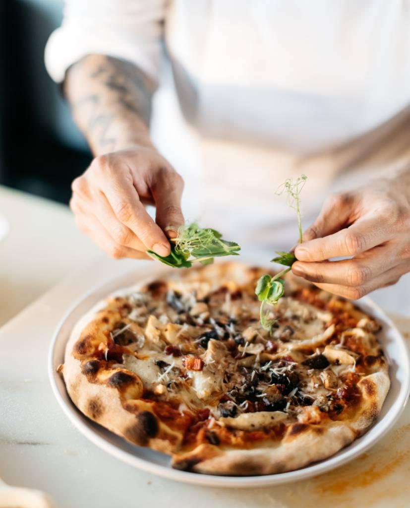 garnishing pizza